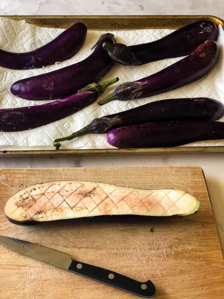 Halved scored and salted eggplant on a cutting board with more eggplant in the background on paper towels