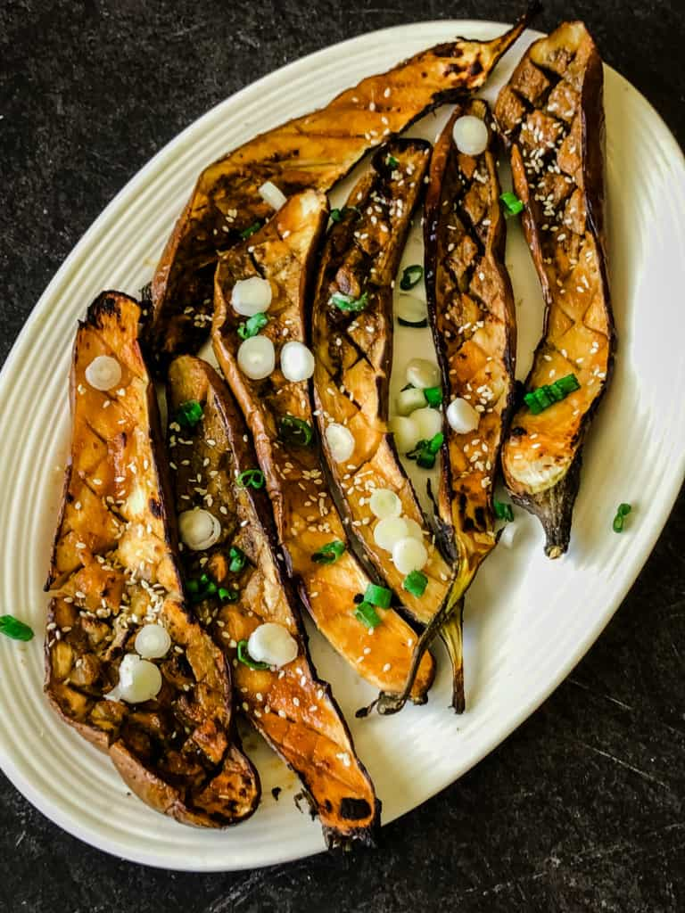 roasted miso glaze eggplant with sliced green onions and sesame seeds on a white platter