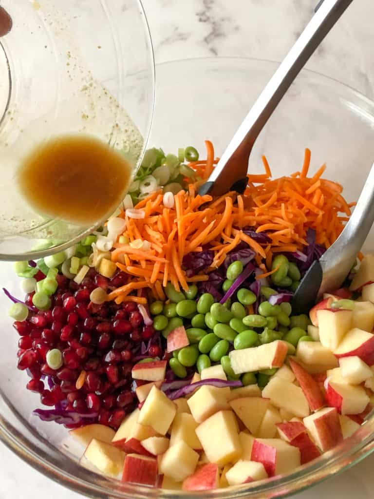 mixing the ingredients for purple cabbage slaw