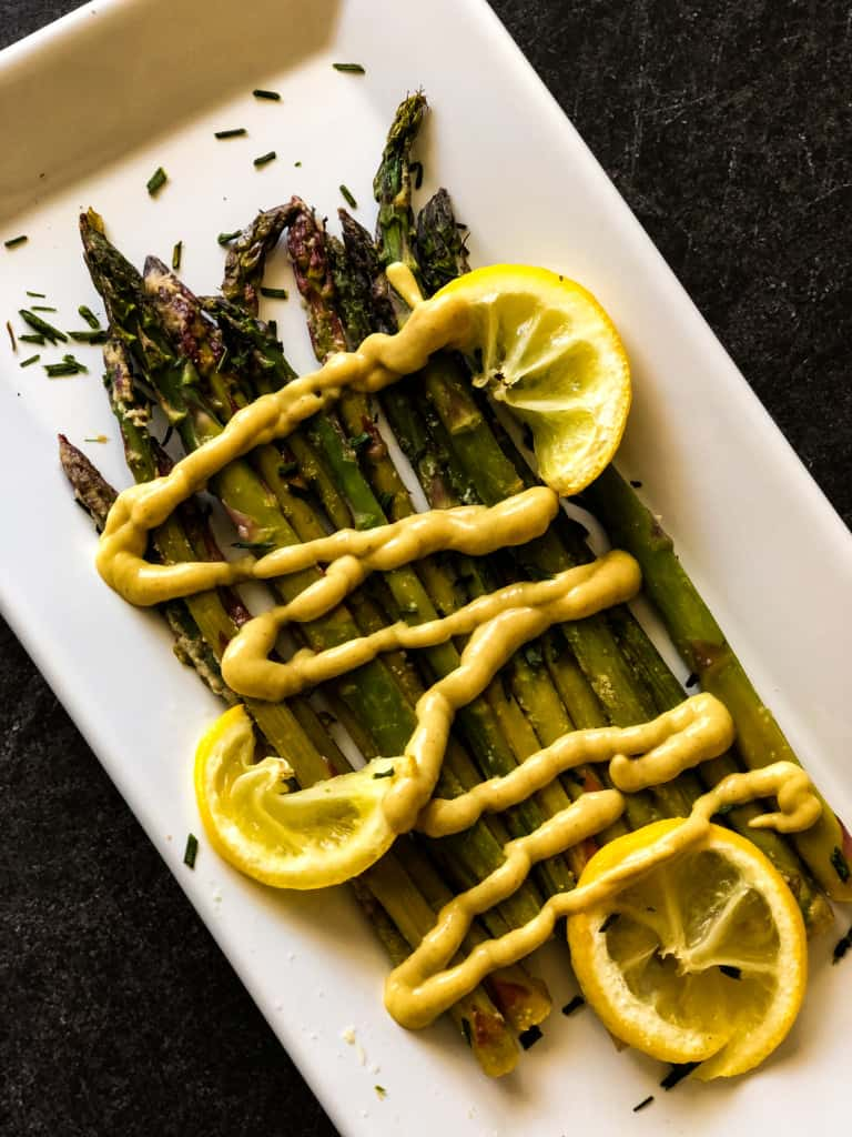 roasted asparagus with vegan honey mustard dressing drizzled on top