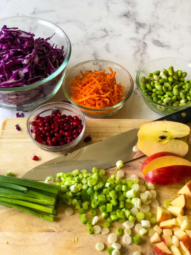 ingredients needed for purple cabbage slaw including shredded purple cabbage, pomegranate seeds, shredded carrots, edamame, chopped apples, and sliced green onions.e