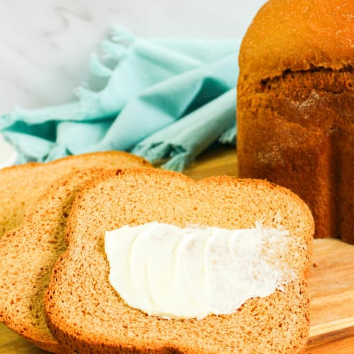 baked wheat bread with slices of buttered bread in foreground