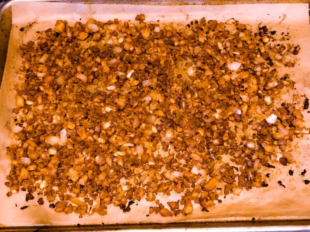 uncooked asian tofu crumbles on parchment lined baking sheet b
