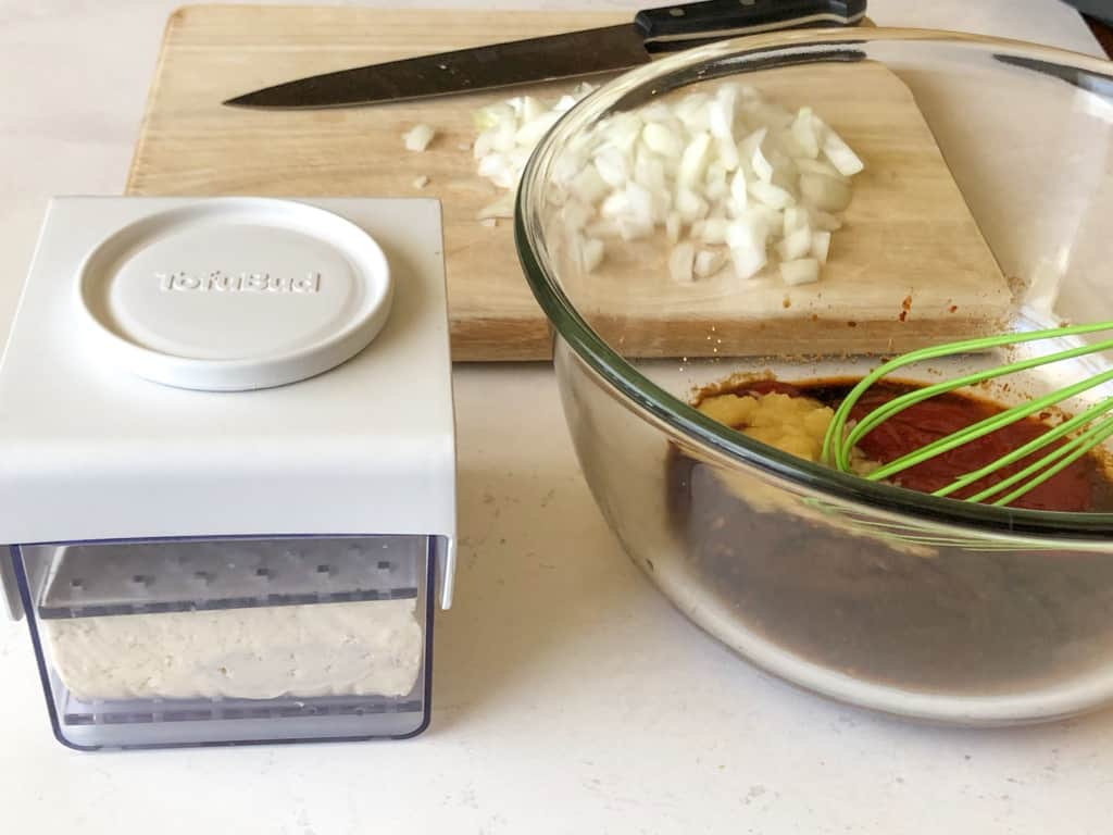 tofu press in front on wooden cutting board with onions, and next with a glass bowl with ingredients for the sauce mixture being whisked in
