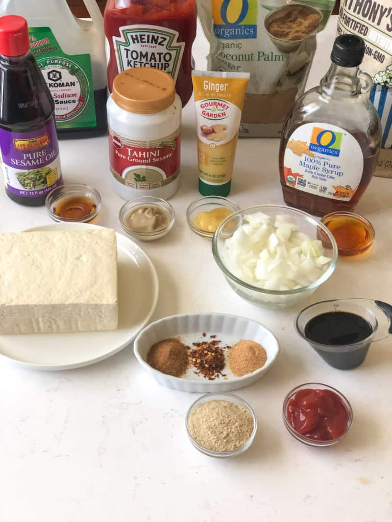 All the ingredients needed for asian tofu crumbles including soy sauce, ketchup, coconut sugar, nutritional yeast, maple syrup, ginger paste, tahini, sesame oil, tofu, chopped onion, smoked paprika, red pepper flakes, roasted garlic powder