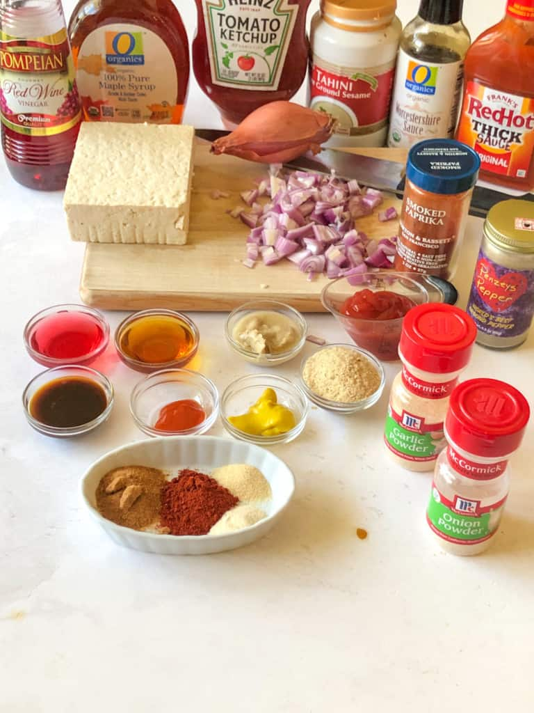 ingredients needed to make bbq tofu crumbles including tofu, red wine vinegar, maple syrup, ketchup, tahini, worcestershire sauce, yellow mustard, hot sauce, nutritional yeast, coconut sugar, smoked paprika, garlic powder, onion powder, salt and pepper