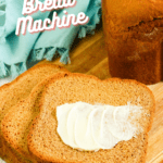 baked wheat bread with slices of buttered bread in foreground with pinterest text overlay