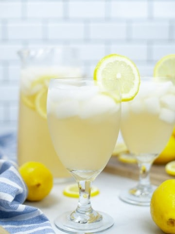 Two glasses of lemonade with a filled glass pitcher