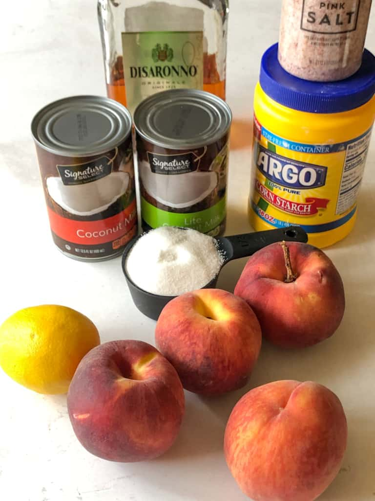 Ingredients needed for peaches and cream ice cream including two cans of coconut milk, sugar, peaches, lemon, cornstarch, amaretto, and a pinch of salt