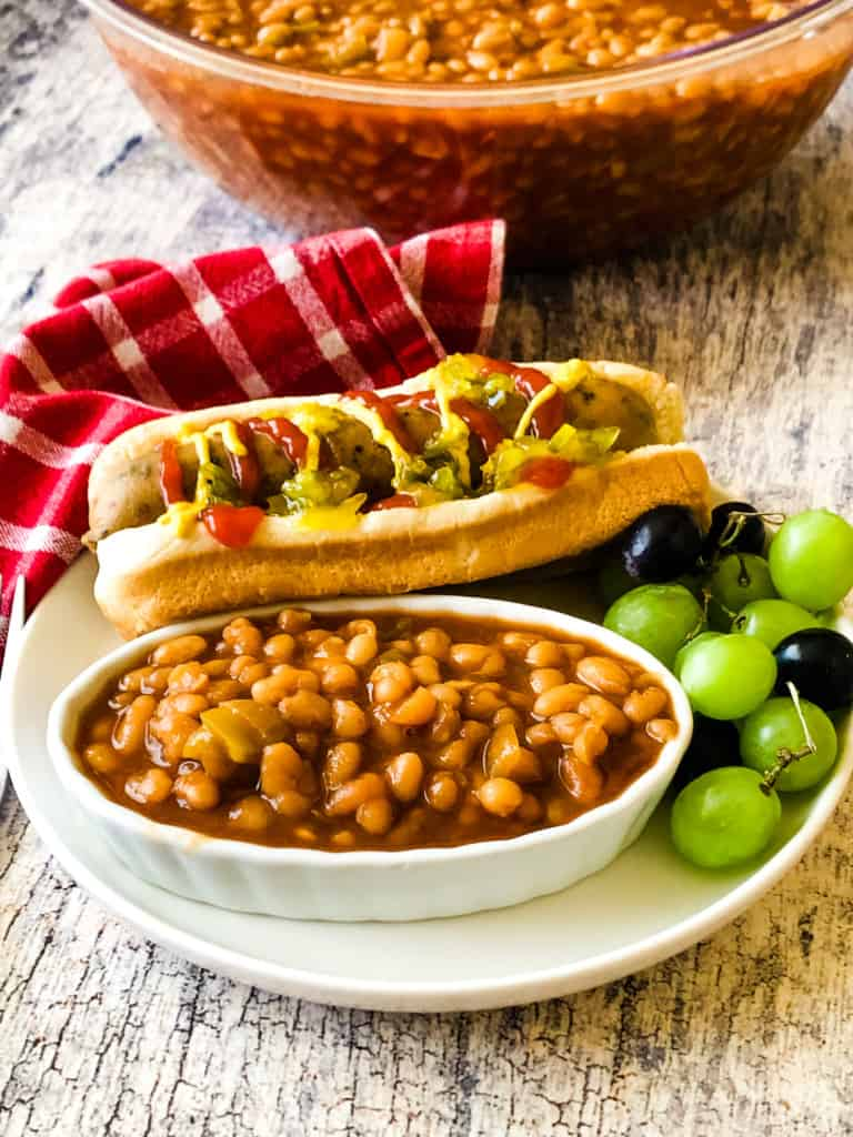 baked beans with vegan hotdog and grades on a plate