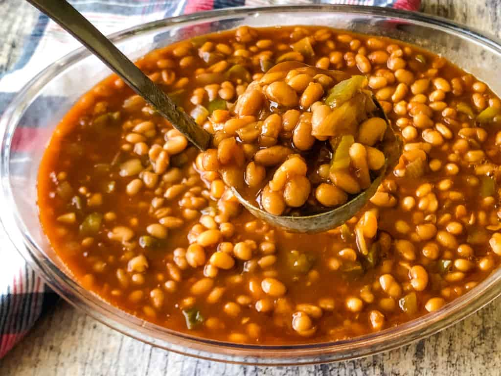 clear serving bowl of BBQ baked beans with a ladle serving out a portion