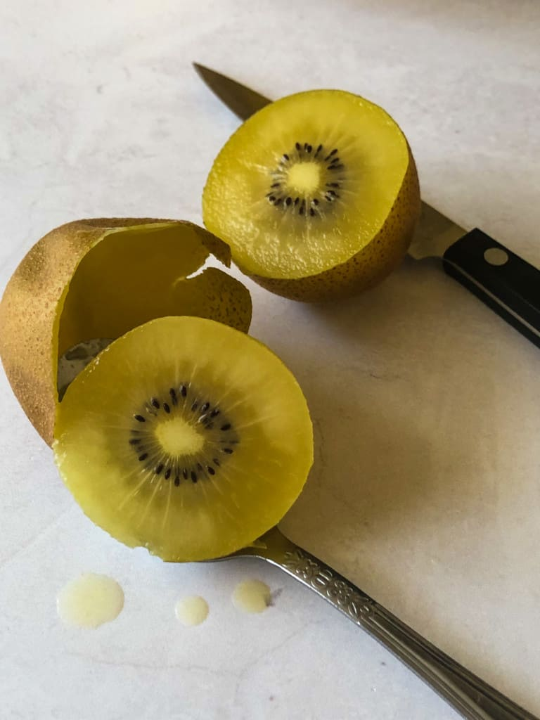 a kiwi cut in half with one half scooped out with a spoon