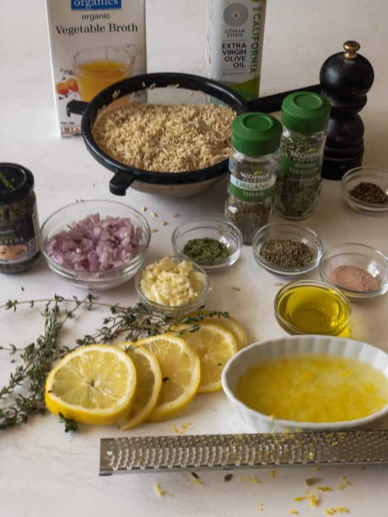 ingredients needed for lemon herbed brown rice including brown rice, vegetable broth, olive oil, tarragon, thyme, black pepper, salt, capers, diced shallots and garlic, with sprigs of fresh thyme and sliced lemons in foreground along with lemon juice and a lemon grater