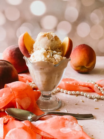 Peaches and cream ice cream in a glass dish with peaches sticking out of the top. a scarf, pearls, and spoon in the foreground. Peaches in the background.