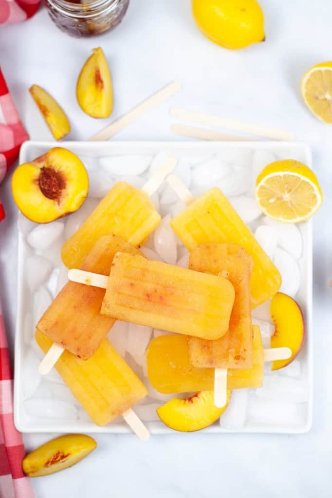 seven frozen peach popsicles on a tray with ice - red napkin and lemons and peaches in background