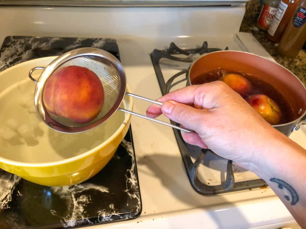 dunking a peach into ice water from the boiling water for easier peeling