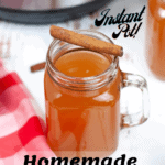 apple cider in glass mug with cinnamon stick on top and instant pot in the background with pinterest text overlay