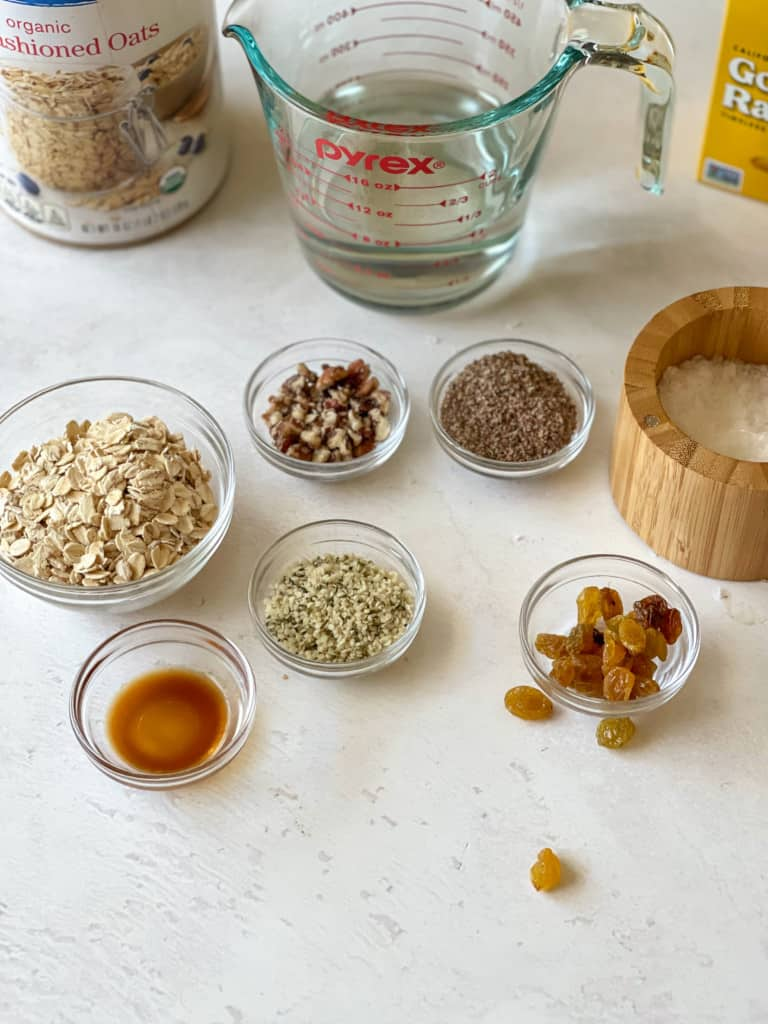 ingredients needed for 2 minute oatmeal including old fashioned oats, water, chopped pecans, ground flaxseed, salt, vanilla, hemp hearts, and raisins