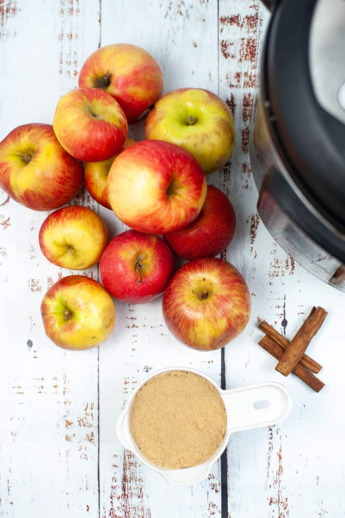 fresh apples, light brown sugar, cinnamon sticks and an Instant Pot ready for making apple cider