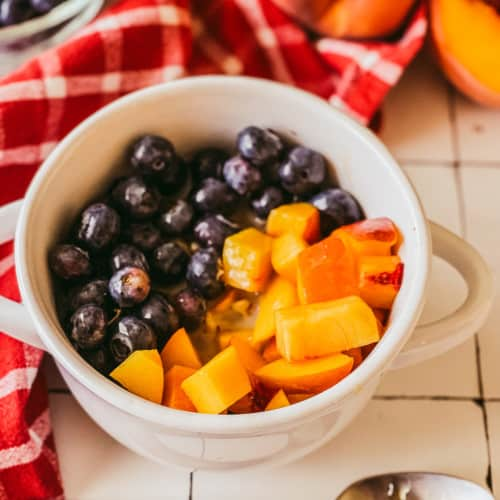 bowl of oatmeal topped with blueberries and peaches