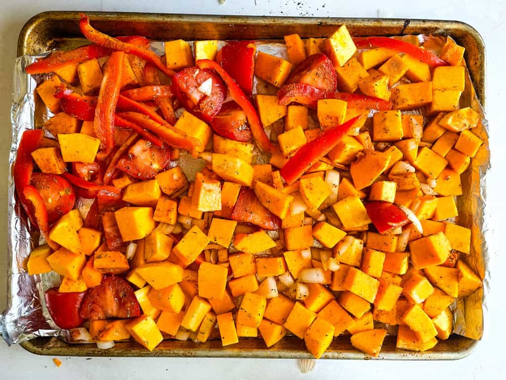 cubed butternut squash, bell peppers, and onions on a pan ready for roasting