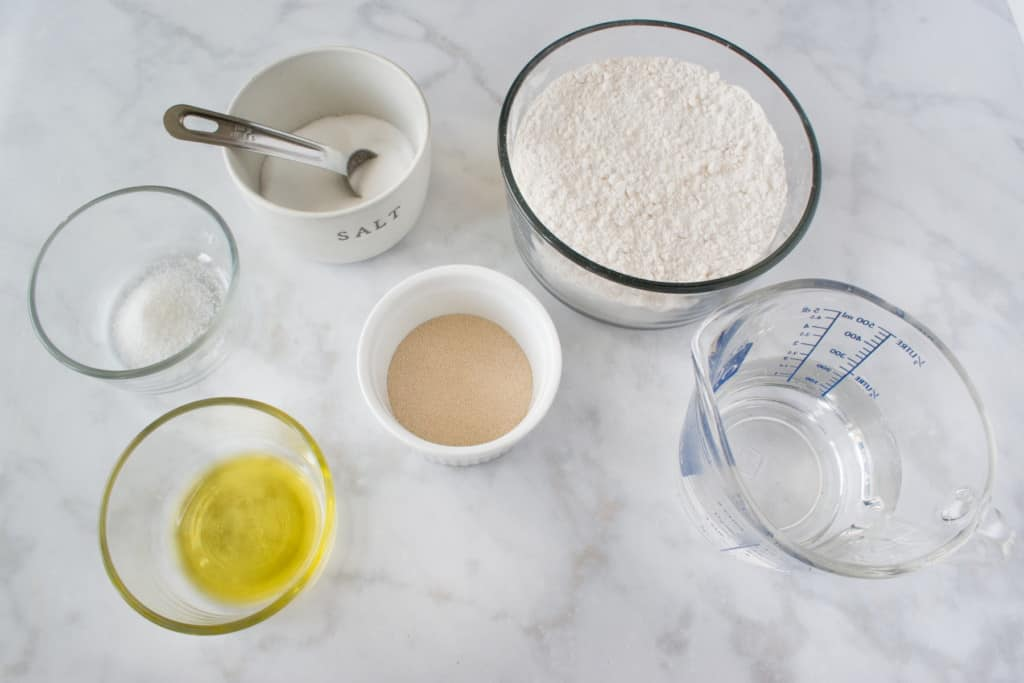 ingredients for pizza dough including olive oil, sugar, salt, yeast, flour, and water