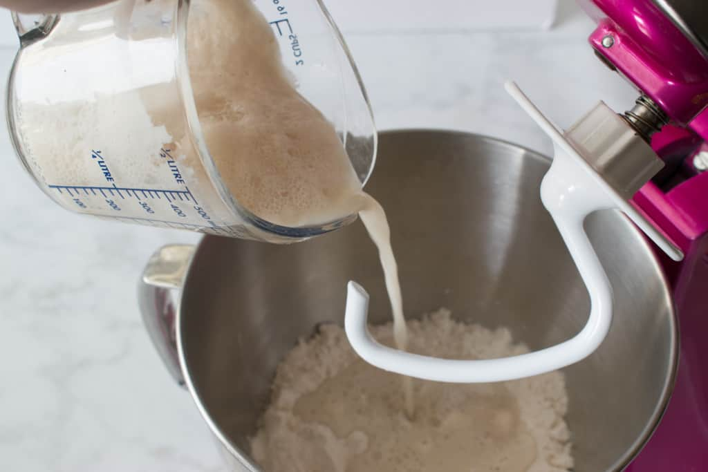 pouring proofed yeast into metal bowl