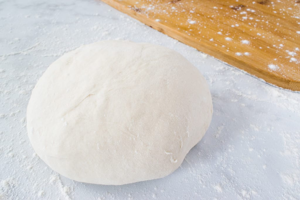 ball of risen pizza dough and floured wooden cutting board