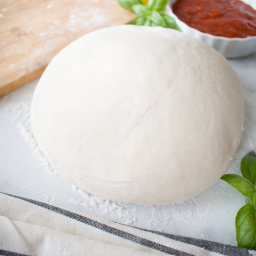 uncooked ball of pizza crust dough with basil leaves , pizza sauce, and olive oil in background