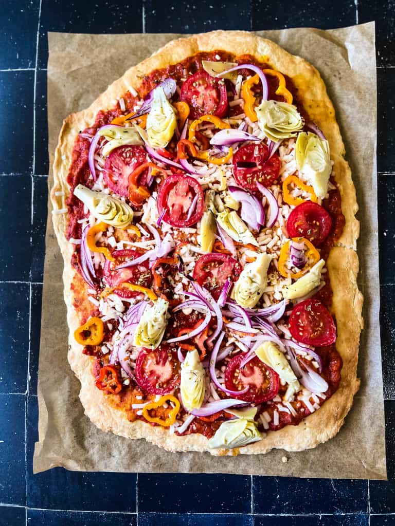cooked veggie pizza on parchment paper. some of the veggies include artichoke hearts, red onion, and tomatoes