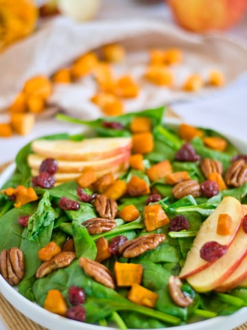 plated autumn salad with apple, pecans, and pumpkin in background