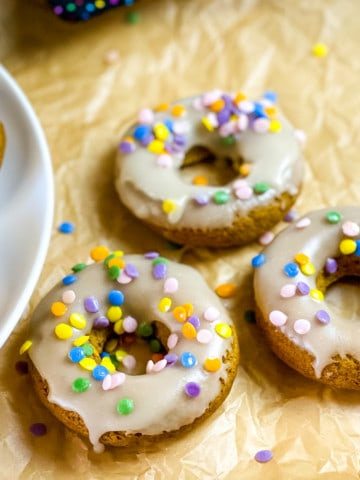 three glazed and sprinkle decorated donuts with white plate and two donuts