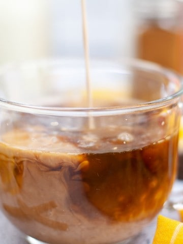 pumpkin spice creamer being poured in glass cup of coffee